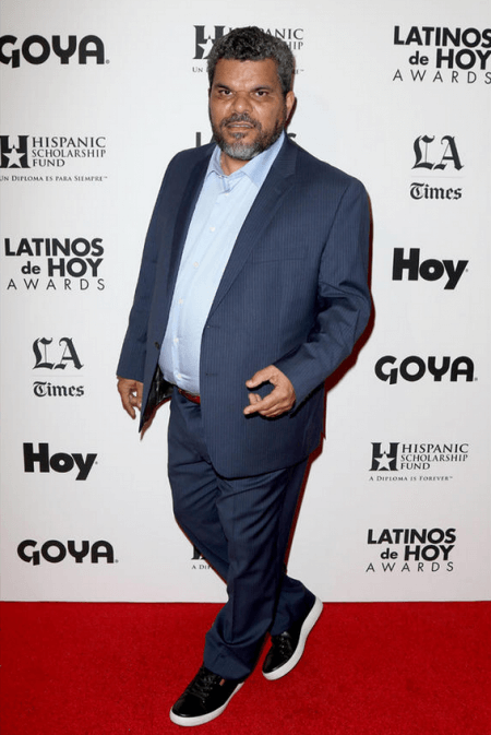 Actor Luis Guzman in front of a step and repeat for the Latinos de Hoy Awards