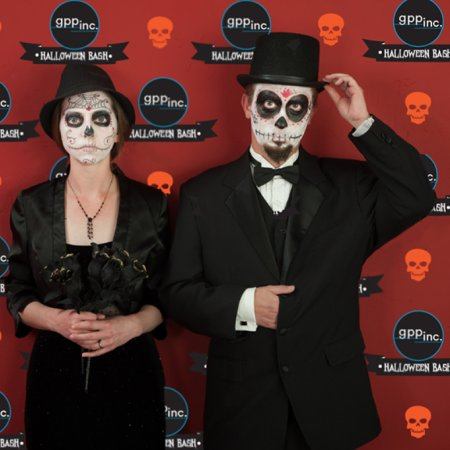 People in front of a spooky step and repeat backdrop