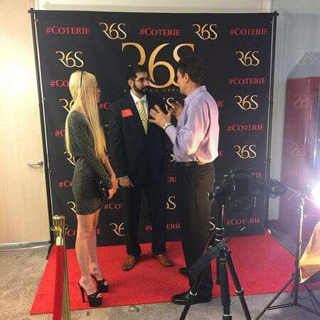 A custom 8 by 8 foot step and repeat with red carpet and stanchions for R6S