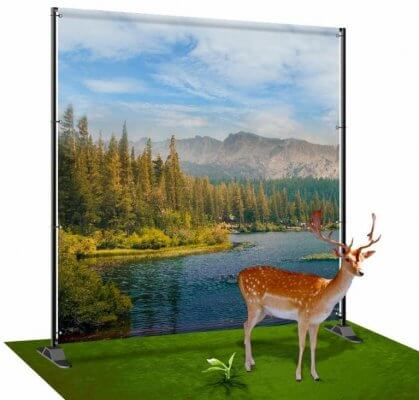 Cut-out deer on a green grass carpet with a river and mountain backdrop that was eco-printed!